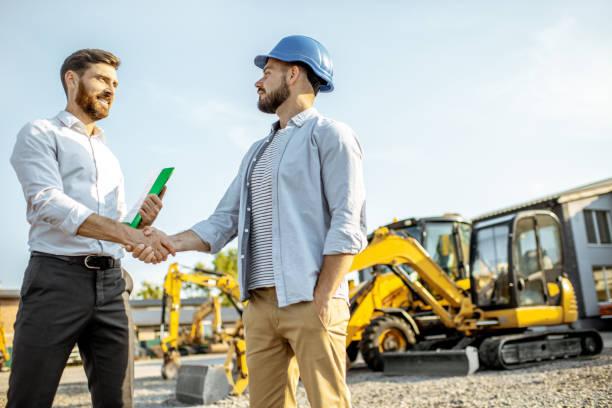 중장비가 있는 매장에서 영업 컨설턴트가 있는 빌더 - 건설 장비 뉴스 사진 이미지