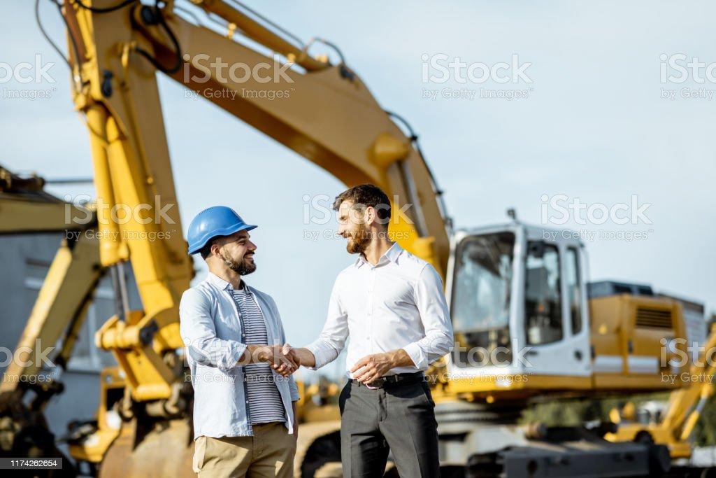 在有重型機械的車間裡,有銷售顧問的建築商 - 免版稅交通方式圖庫照片
