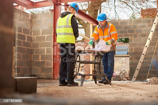 builder checking plans of home extension