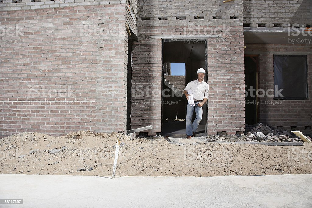 Builder with blueprints on construction site royaltyfri bildbanksbilder
