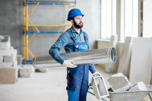 Builder with pipe indoors stock photo