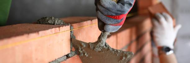 Builder mit Spachtel, um überschüssigen Zement zu entfernen – Foto