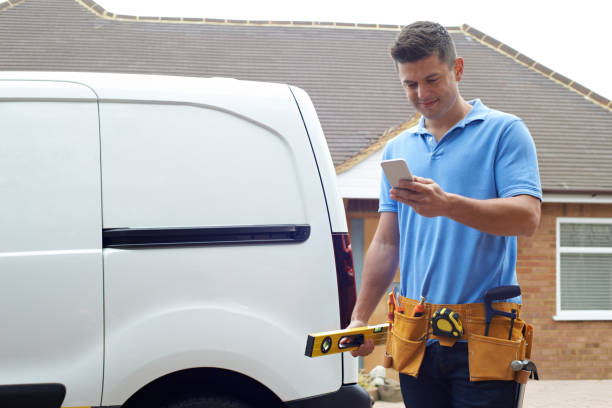 Builder With Van Texting On Mobile Phone Outside House stock photo