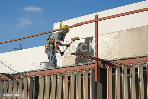 istock builder worker painting facade of high-rise building with roller 1056897332