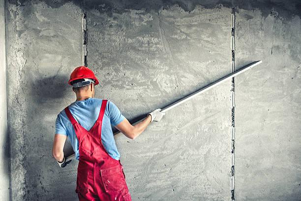 builder arbeiter plastering fassade industriegebäude mit leveler - verputz stock-fotos und bilder