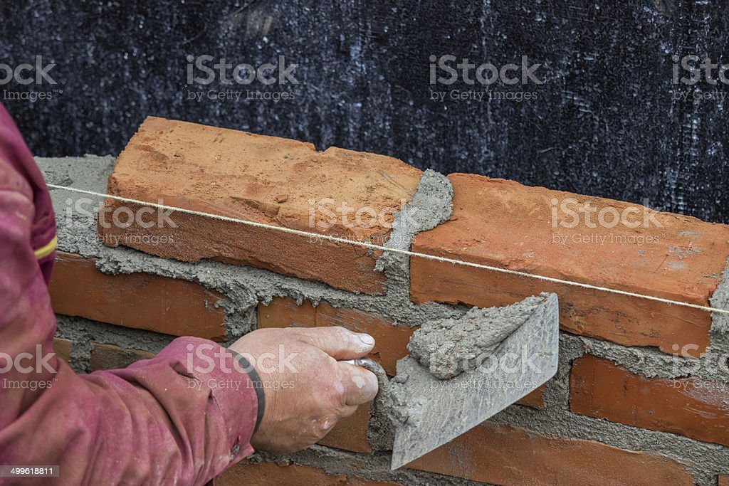 Builder worker using the sharp end of the trowel stock photo