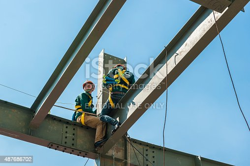 istock Builder workers in safety protective assemble metal construction frame 487686702