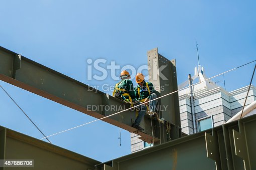 istock Builder workers in safety protective assemble metal construction frame 487686706