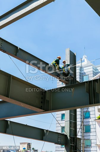 istock Builder workers in safety protective assemble metal construction frame 487686708