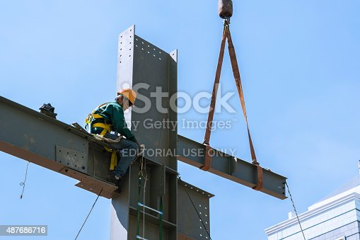 istock Builder workers in safety protective assemble metal construction frame 487686716