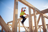 Builder working on rooftop frame of wooden construction building.