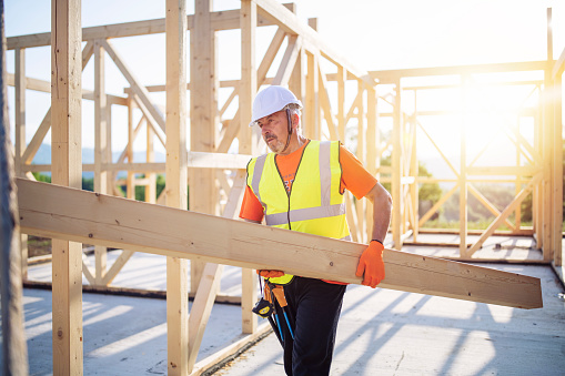 Side view of builder holding wooden beam, working on unfinished wooden house at sunset.