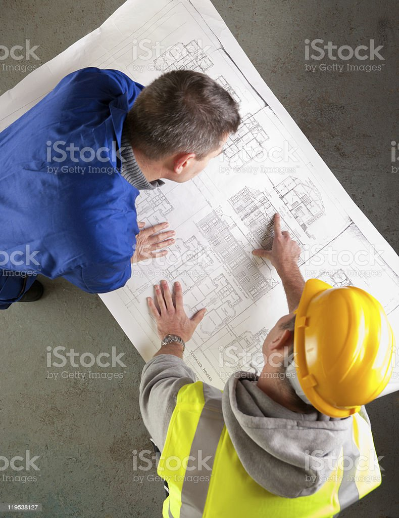 Builders examine blueprints royalty-free stock photo