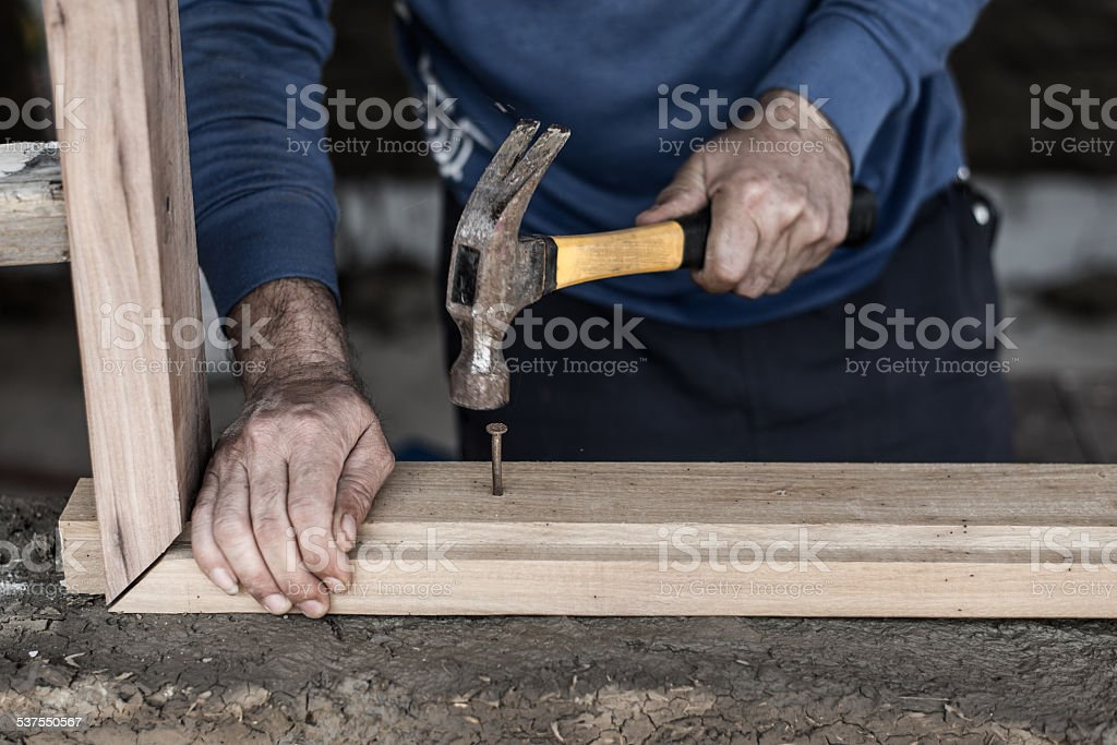 Builder's hands hammering stock photo