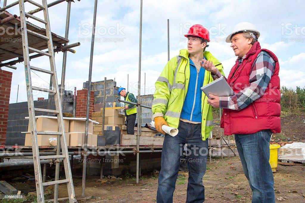 Builders Looking at Digital Tablet stock photo