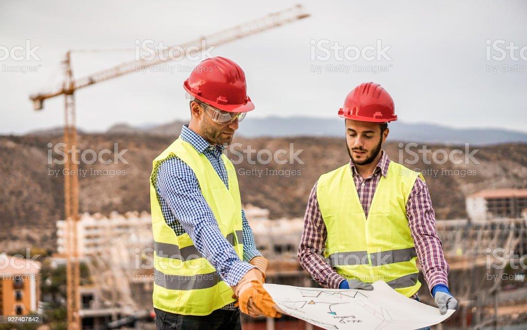 Bauherren auf Wohnungsbau-Website suchen, das Bauvorhaben - Arbeiter sind zufrieden mit ihrem Plan - Umgang, Immobilien, Ingenieur und industrielles Konzept - konzentrieren sich auf linke Mann Gesicht – Foto