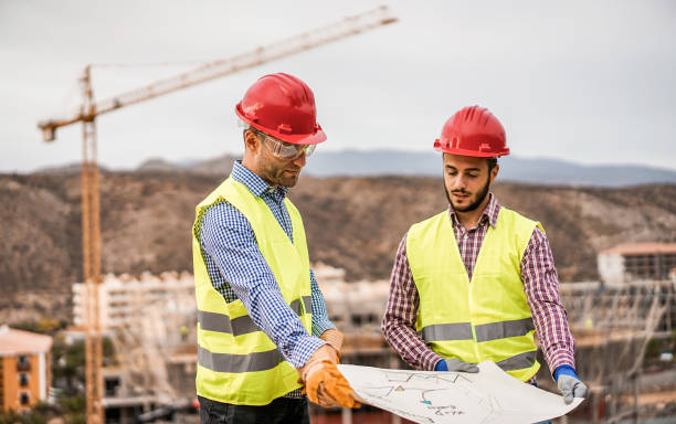 Builders on residential construction site looking the building project  - Workers are satisfied of their plan - Dealing, real estate, engineer and industrial concept - Focus on left man face stock photo
