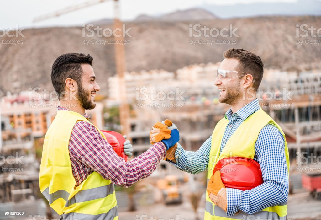 Builders on residential construction site making a deal - Happy workers are satisfied of their plan - Dealing, real estate, engineer, industrial and building houses concept royalty-free stock photo