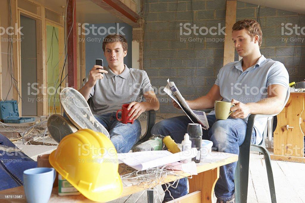 Builders Relaxing During Break On Site stock photo