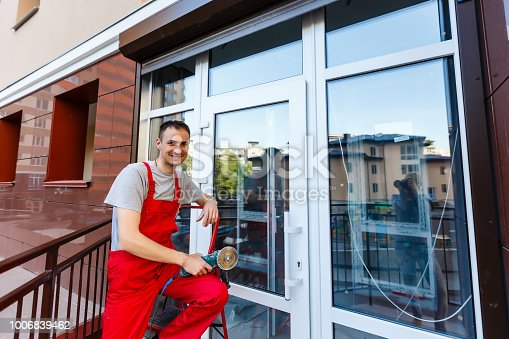 945456460 istock photo builders worker installing glass windows on facade of business building using glass suction plates 1006839462