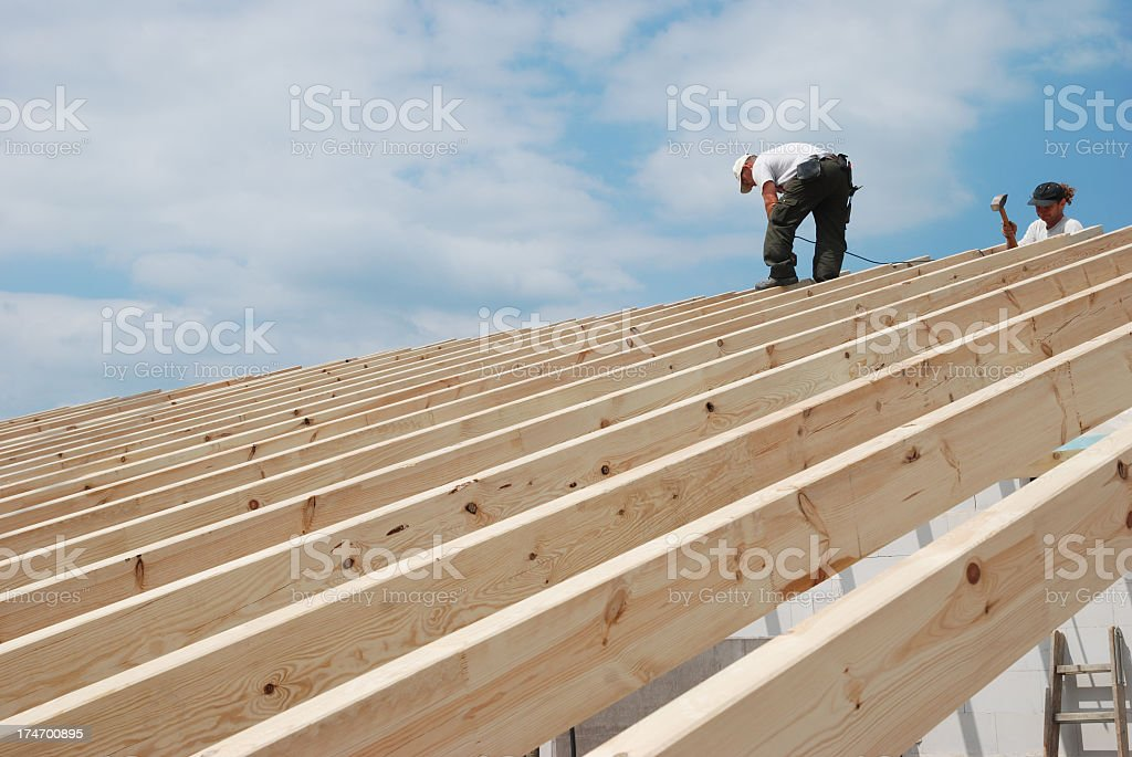 Builders working on constructing a roof stock photo