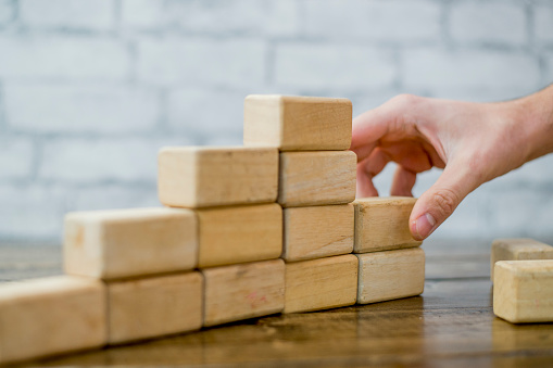 An anonymous hand adds blocks to a 3D graph of business growth.