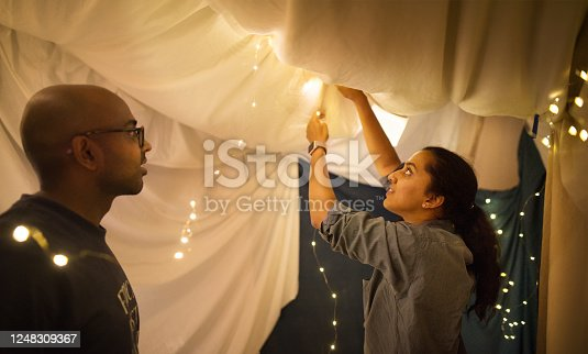 Shot of a couple adding lights to a tent made in their living room