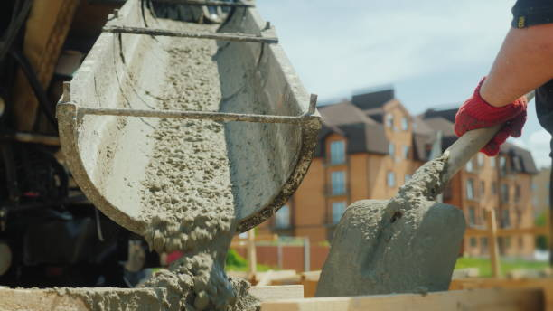 Building a cottage. Workers take concrete from a mixer into a wooden formwork Building a cottage. Workers take concrete from a mixer into a wooden formwork. mixing stock pictures, royalty-free photos & images