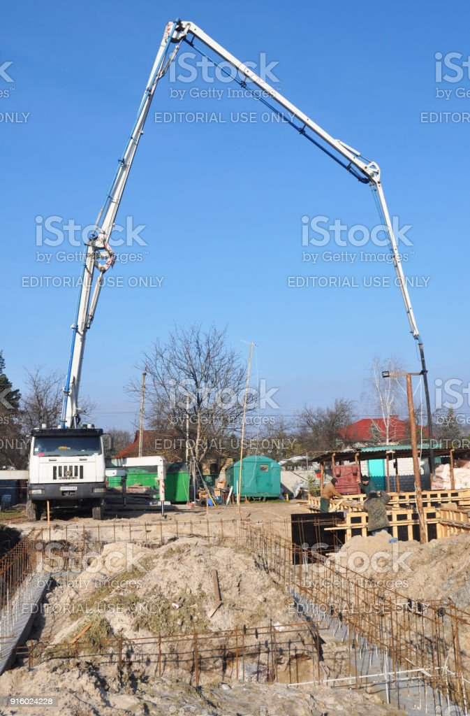 Building a foundation. Contractors making a concrete slab, house foundation with car with pump tube. Pouring a concrete slab along the foundation stock photo
