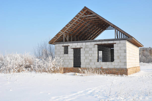 building a home during winter. building new house from autoclaved aerated concrete blocks vs bricks with unfinished roofing metal tiles construction. - contributor stock pictures, royalty-free photos & images