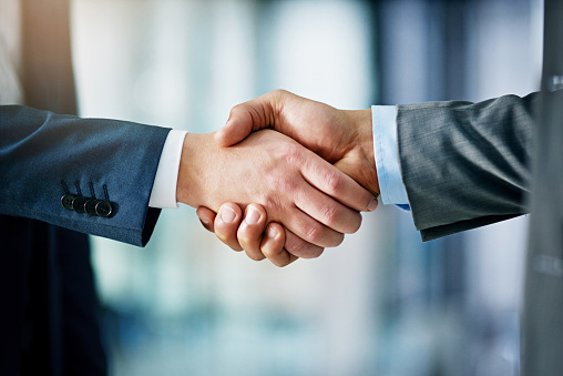 Closeup shot of two businessmen shaking hands in an office