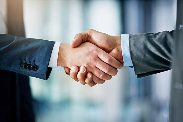 Building a network towards success Closeup shot of two businessmen shaking hands in an office alliance stock pictures, royalty-free photos & images