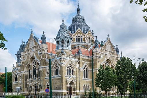 View of the building of the new Synagogue in Szeged against the blue sky with clouds.