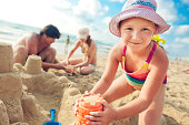 Young happy family building a sandcastle.