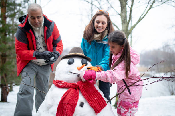 mit ihrer familie einen schneemann bauen - schneemann bauen stock-fotos und bilder