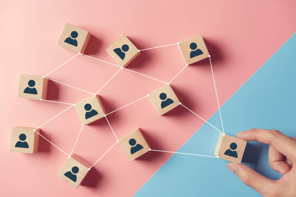 Building a strong team, Wooden blocks with people icon on pink and blue background, Human resources and management concept. stock photo