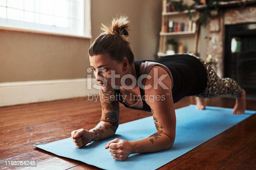 Shot of a young woman exercising at home
