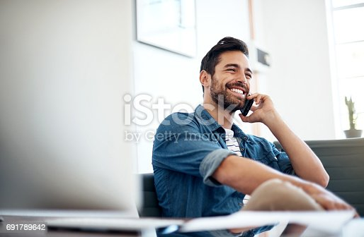 Cropped shot of a young designer talking on a cellphone in an office