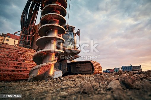 Building activity on contruction site. Close-up view of drilling machine against trucks.