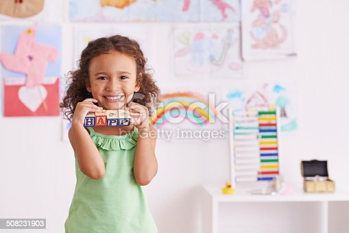 Shot of a cute little girl playing with alphabet blocks