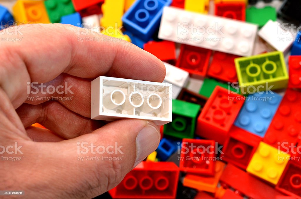 Building blocks Mans hand holds a red toy block against mix of building blocks background. concept photo of imagination, creativity, planning and ideas 2015 Stock Photo