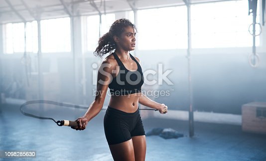 Cropped shot of an attractive and athletic young woman jumping rope in the gym