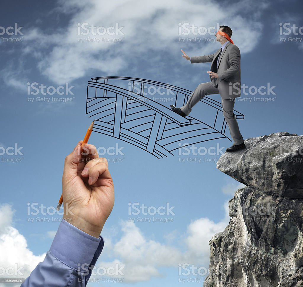 Building bridges - assistance for business Businessman in a blindfold stepping off a cliff ledge with giant hand drawing a bridge for a safe crossing concept for building bridges, risk, challenge, conquering adversity, ignorance and assistance Fear Stock Photo