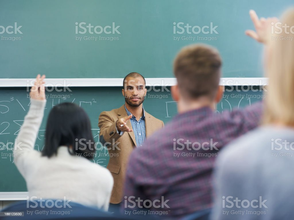 Building bright minds Shot of a young male teacher giving a lesson to his students on the lecture hall 20-29 Years Stock Photo