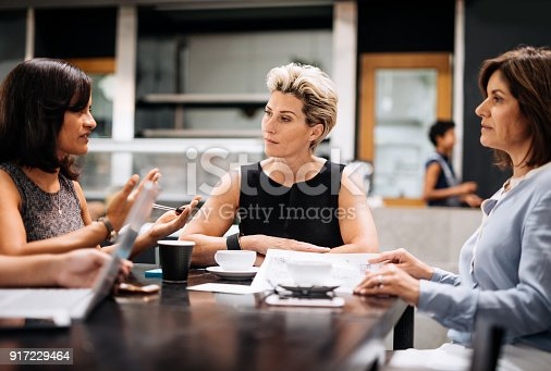 Group of professionals, mostly businesswomen, coming to snack bar or cafeteria for a coffee break. Businesswomen having an informal business meeting during the coffee break, but also having leisure time together.