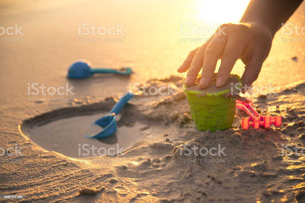 building castle on beach with toy in sunset stock photo