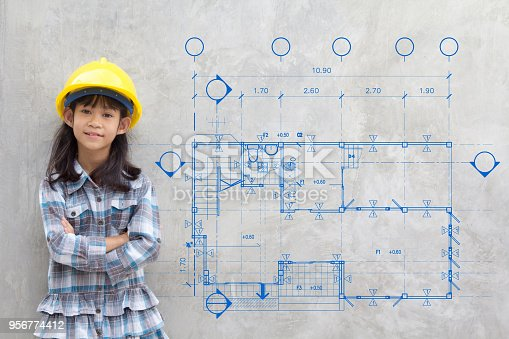 istock building, childhood, developing, construction and architecture concept - smiling little girl in yellow helmet showing blueprint drawing on wall 956774412