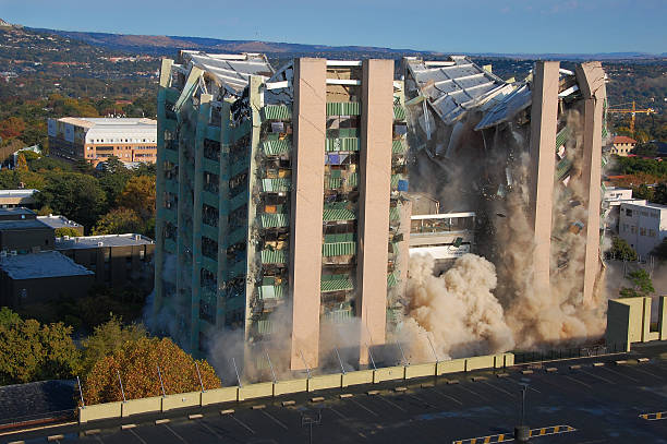 Building collapses from a planned demolition  Building demolition by implosion - image 5 of a 10 shot sequence collapsing stock pictures, royalty-free photos & images