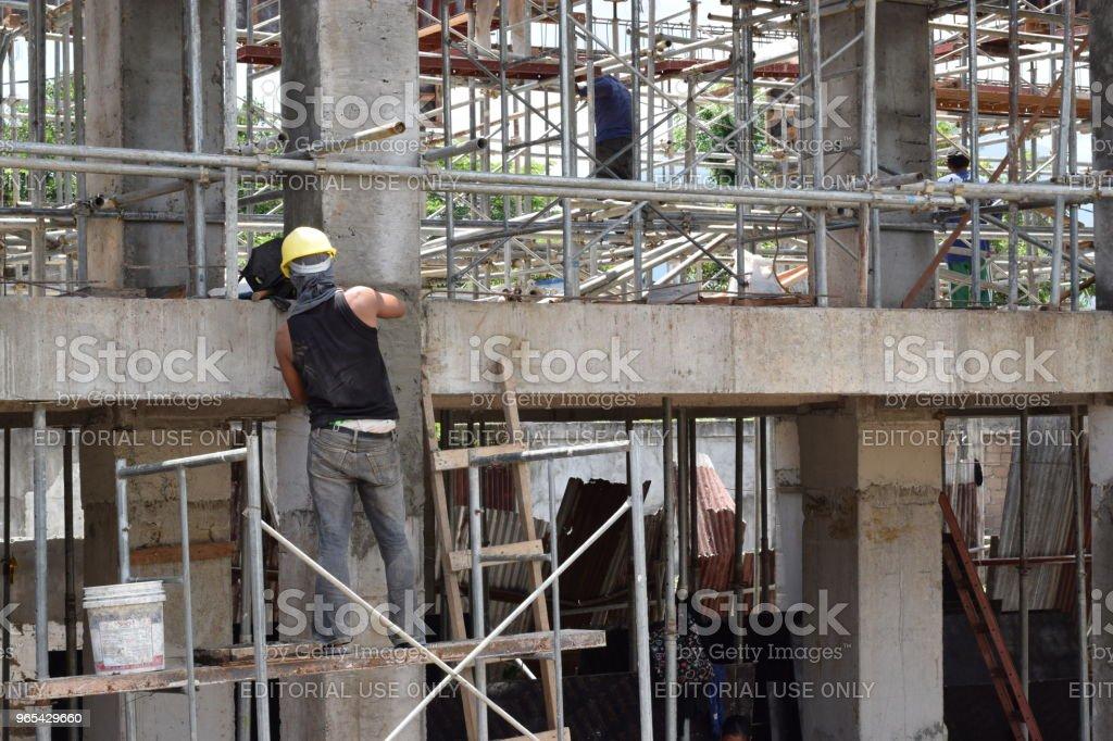 Maçon de construction de bâtiment des travaux de plâtrage debout sur les tubes d'échafaudage sur chantier - Photo de Acier libre de droits