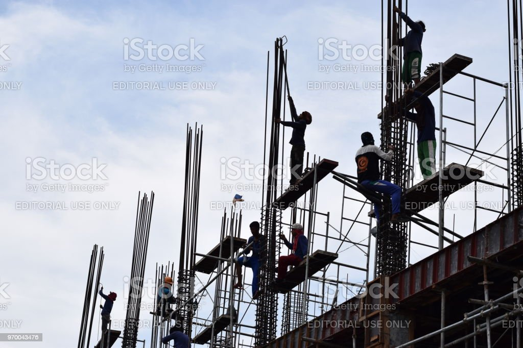 Building construction steel-men working joining column steel pieces on-board scaffolding pipes on high rise building stock photo
